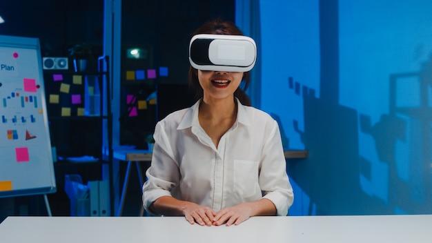Молодая азиатская дизайнерская женщина в очках vr (виртуальная реальность) тестирует мобильное приложение от разработки программного обеспечения в ночь современного творческого домашнего офиса. социальное дистанцирование, карантин для предотвращения вируса короны.