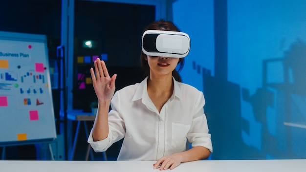 Young asian designer female using vr glasses (virtual reality) testing mobile app from develop software at modern creative home office night. social distancing, quarantine for corona virus prevention.
