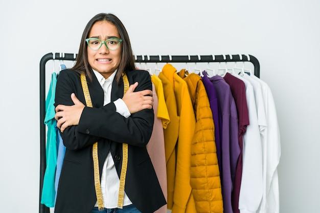 Молодая азиатская дизайнерская женщина, изолированная на белой стене, остывает из-за низкой температуры или болезни.