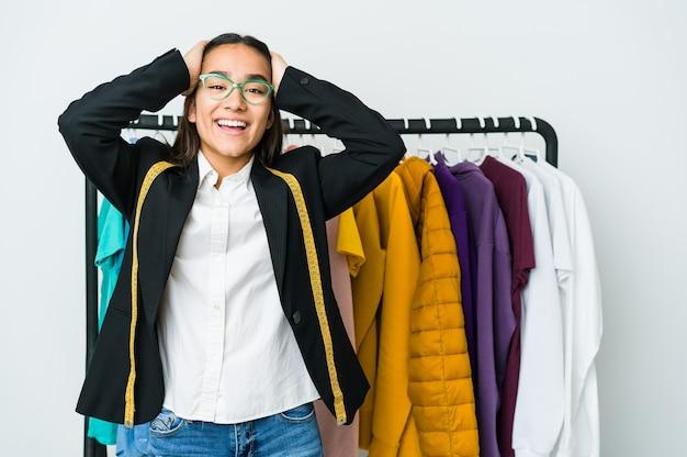 Молодая азиатская дизайнерская женщина изолированная на белой стене радостно смеется, держа руки на голове. концепция счастья.