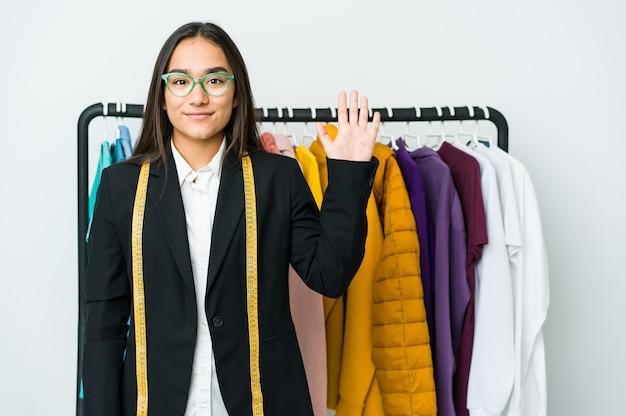 Молодая азиатская дизайнерская женщина изолированная на белой стене усмехаясь жизнерадостная показывая номер пять с пальцами.