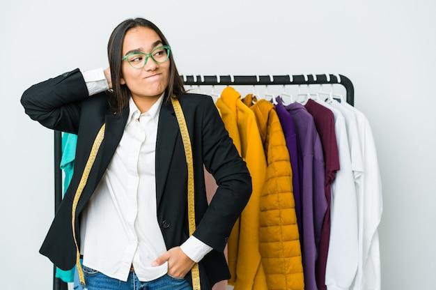 Молодая азиатская дизайнерская женщина изолированная на белой стене касаясь затылка, думая и делая выбор.