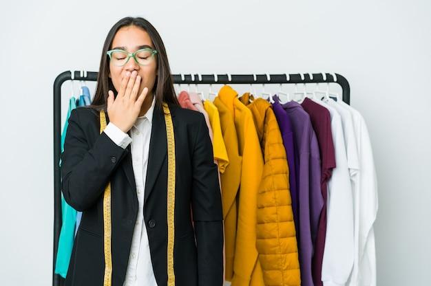 手で口を覆う疲れたジェスチャーを示すあくびをする白い壁に分離された若いアジアのデザイナーの女性