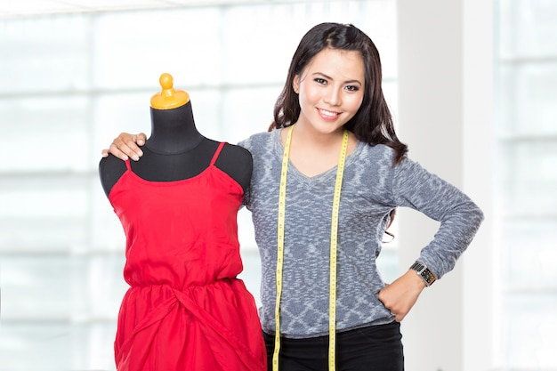 Молодая азиатская дизайнерская женщина представляя усмехаться, держит ножницы