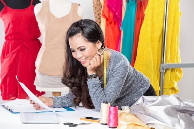 Молодая азиатская дизайнерская женщина используя компьтер-книжку и усмехаться