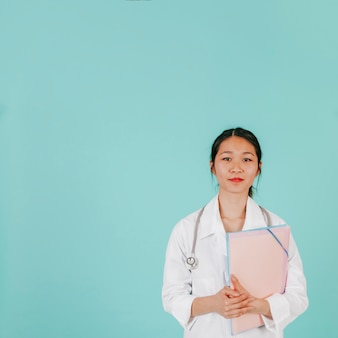 Young asian doctor with stethoscope and folder