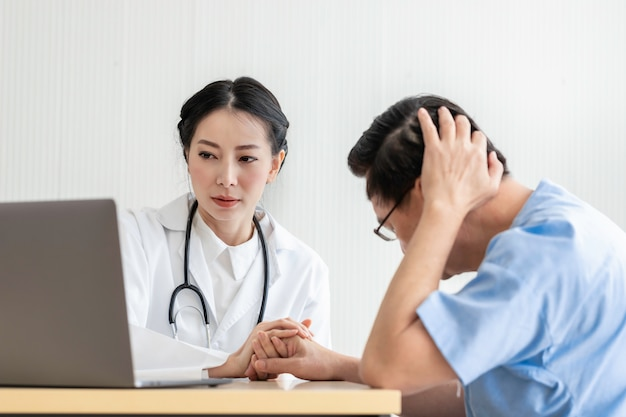 Young asian doctor woman reassuring and discussing senior patient man in the hospital room.