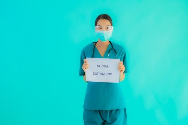 若いアジアの医師の女性着用マスクショーペーパーボード上の社会的距離