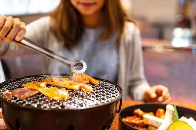 레스토랑에서 한국 바베큐 야키니쿠를 먹는 젊은 아시아