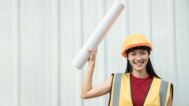 A young asian engineer holds a white board sign for writing messages or announcements against a backdrop of metal sheet at the job site. leader concept.