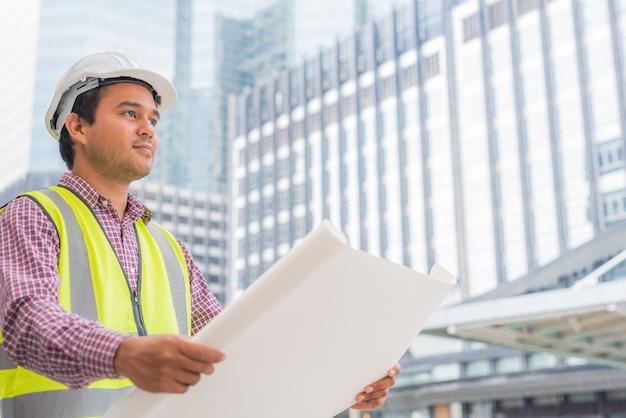 建物のレイアウトプランを探して保持している若いアジアエンジニア