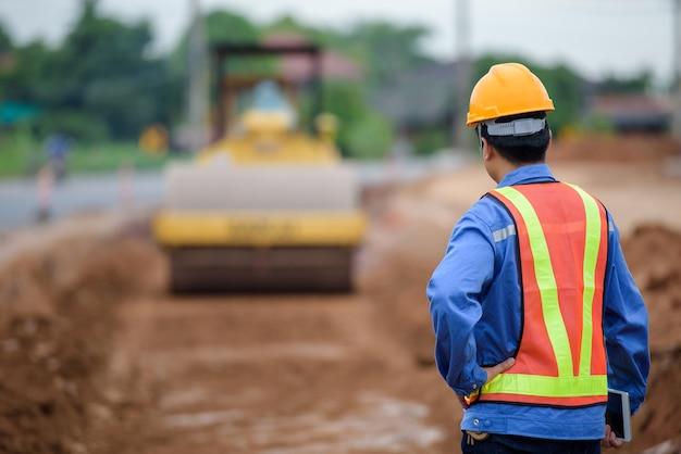 若いアジア人エンジニアが道路建設を監督し、建設現場で道路建設を検査します。
