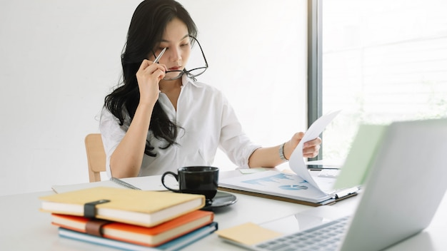 Young asian entrepreneur cogitating thinking making important decision at workplace. concentrated serious office worker millennial woman analysing results