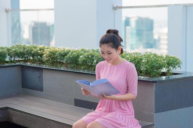Молодая азиатская исполнительная женщина стоя и держите папку вне офисного здания, красивая азиатская бизнес-леди прочитала папку документа внешнюю.