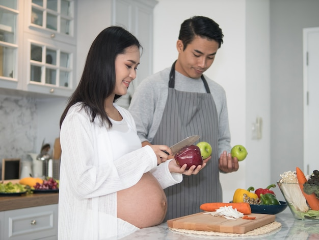 Young asian expecting pregnant couple cooking together in the kitchen at home.
