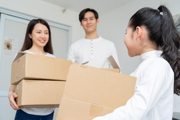 젊은 아시아 가족들이 함께 새 집으로 이사하고 있습니다