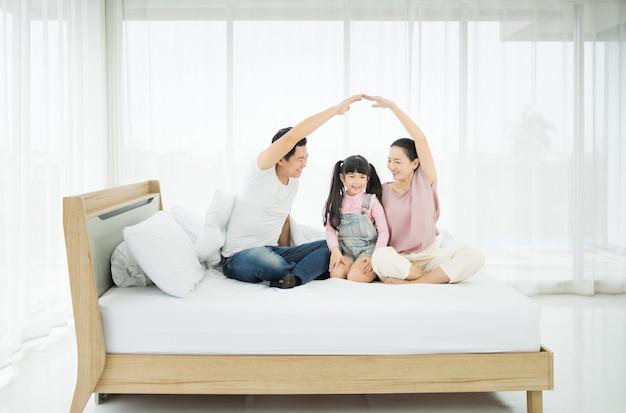 젊은 아시아 가족, 아빠 엄마와 딸 집에서 침대에 장난이 되.