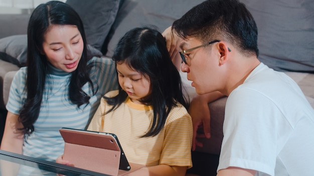 Young asian family and daughter happy using tablet at home. japanese mother, father relax with little girl watching movie lying on sofa in living room. funny parent and lovely child are having fun.