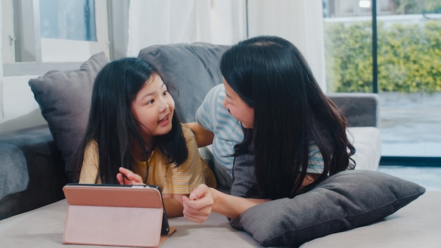 Young asian family and daughter happy using tablet at home. japanese mother relax with little girl watching movie lying on sofa in living room at house. funny mom and lovely child are having fun.