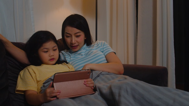 Young asian family and daughter happy using tablet at home. korean mother relax with little girl watching movie lying on sofa before going to sleep in living room at modern house in night.