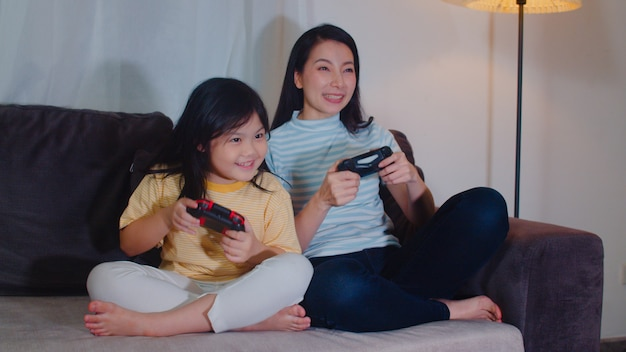 Young asian family and daughter play games at home in night. korean mother with little girl using joystick funny happy moment together on sofa in living room. funny mom and lovely child are having fun