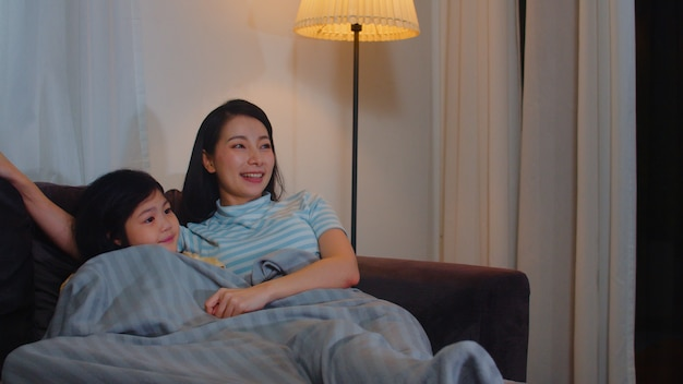 Young asian family and daughter watching tv at home in night. korean mother with little girl happy using family time relax lying on sofa in living room. funny mom and lovely child are having fun.