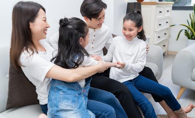 若いアジアの家族は自由な時間に家で楽しませてくれました