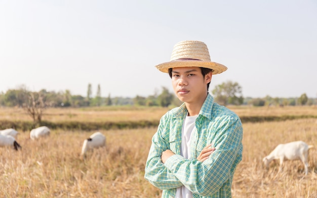 Young asian farmer man standing with arms crossed blurred goats eating grass in field, smart farmer concept