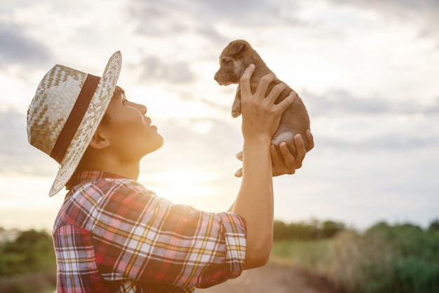 Young asian farmer playing with his brown small pup in the evening after work