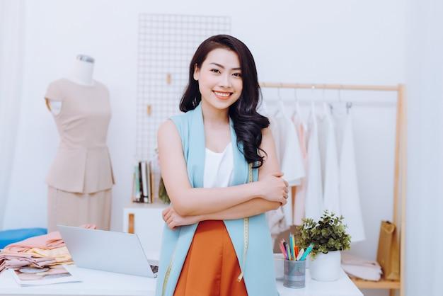 Молодой азиатский модельер улыбается и стоит перед столом в мастерской