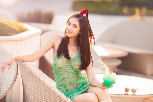 ビーチバーでカクテルを飲む若いアジアのファッションの女性。