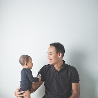 Молодой азиатский отец держит его прелестный ребенок