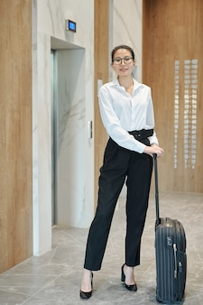 Young asian female business traveler with suitcase standing by elevator door while going to booked hotel room