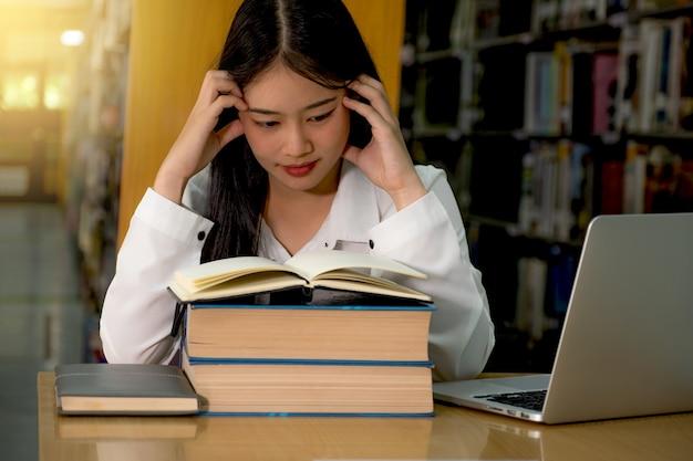 젊은 아시아 여대생들은 책 연구를 읽고 도서관에서 교과서에서 배운다