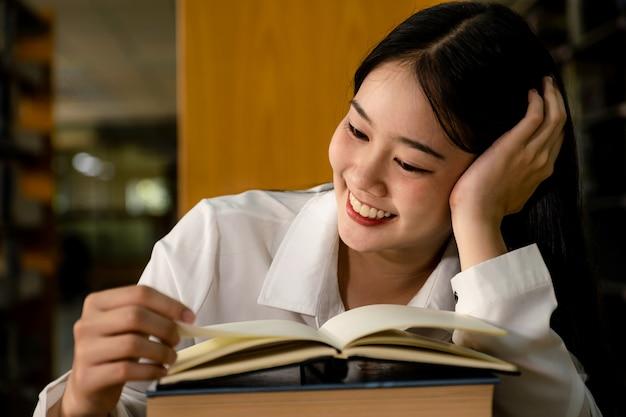 Молодые азиатские студентки колледжа смотрят, как читают книги, исследуют и учатся по учебникам в университетской библиотеке.