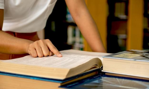 젊은 아시아 여성 대학생 손 연구를 위해 책을 가리키고 교과서에서 배울
