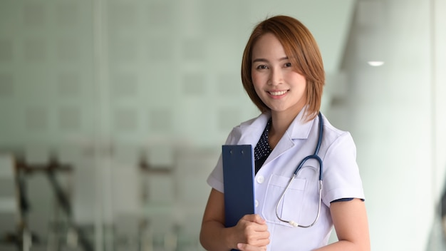 Young asian female doctor on modern clinic background.