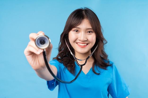 젊은 아시아 여성 의사는 청진기를 행복하게 웃고 필요
