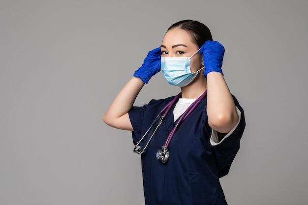 젊은 아시아 여성 의사는 흰 벽에 격리된 의료용 마스크를 쓰고 있다