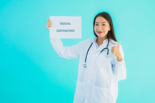 社会的距離のサイン紙と若いアジア女性医師