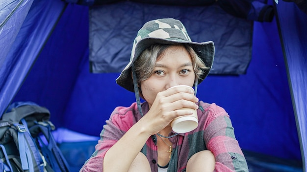 Young asian female drink coffee in tent camping