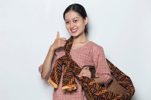 白い背景の上の親指を示す若いアジアの女性農家