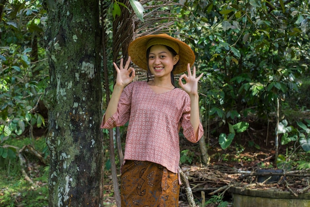 Young asian female farmer showing thumb in rice field