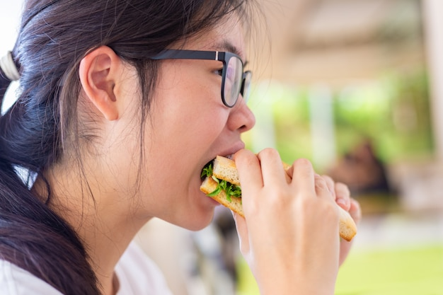 Young asian female holding her salmon sandwich while eating deliciously