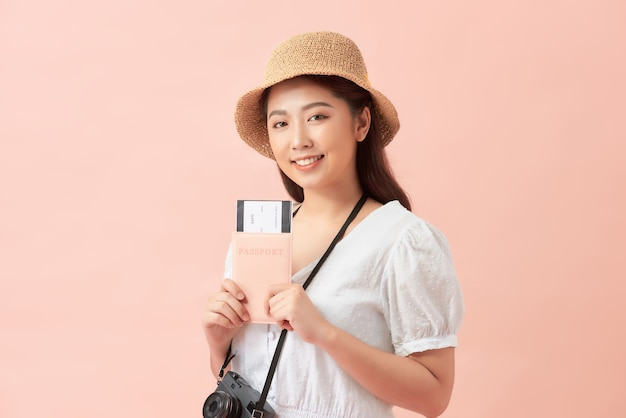 Young asian female isolated on pink holding airplane tickets