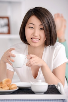 Young asian female lying on bed and eating.