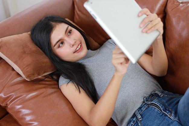 幸せな顔とタブレットを使用して、リビングルームのソファに横たわって若いアジアの女性