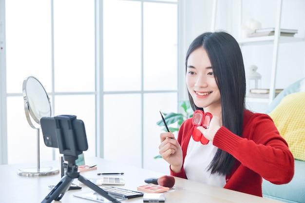 Молодая азиатская визажистка, бьюти-влогер или блогер записывает видеоурок по косметическому макияжу