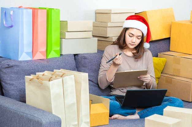 Young asian female online seller entrepreneur, wearing christmas hat, working on her online business