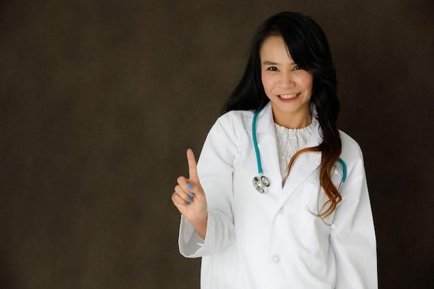 청진기를 가진 젊은 아시아 여성 의사는 어두운 회색 배경에서 보이지 않거나 가상 현실 버튼을 만지는 것처럼 보입니다.